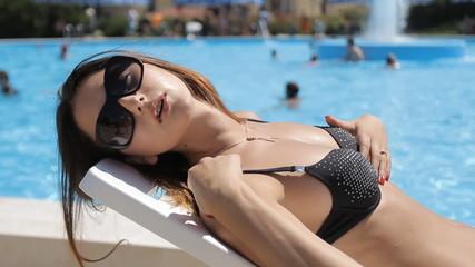 Glamorous sexy girl on black swimsuit sunbathing on deckchair