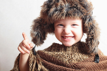 smiling child in fur Hat.fashion winter style.little funny boy