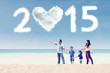 Family walking at beach under cloud of 2015