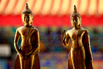 2 golder buddha scultures in standing posture with spider web
