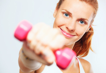 Young woman with dumbbells in her hands.