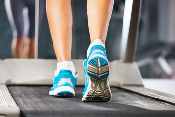 Woman running on treadmill in gym.