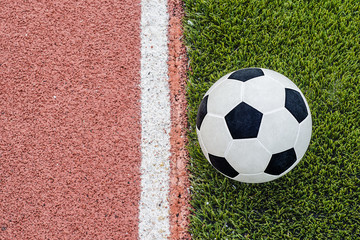 The one football is near the line on the artificial grass field