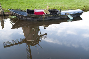 Little boat and reflection of Dutch windmill in the water