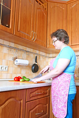 Woman housewife with a knife cut vegetables
