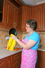 Woman housewife cleans the pan