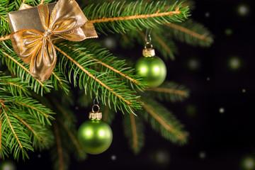 Grüne Weihnachtskugeln an Tannenbaum vor schwarzem Hintergrund
