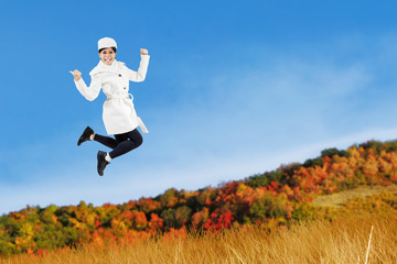 Woman jumping with an autumn jacket