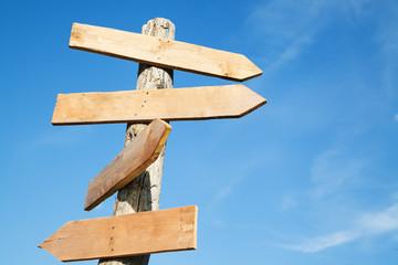 Blank wooden arrow shape signs against blue sky