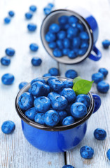 Delicious blueberries in cups on table