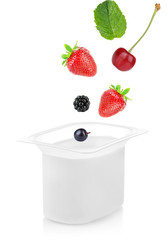 Delicious fresh berries falling into yogurt isolated on white
