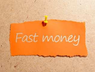 "Paper sheet with inscription ""Fast money"" on wooden background"