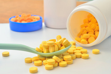 yellow medicine tablet on the spoon and open bottle of medicine