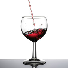 Red wine pouring, slanted horizon, perspective effect.