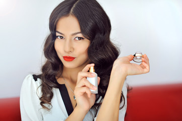 Woman with perfume, young beautiful girl holding bottle of perfu