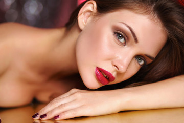 Close-up portrait of beautiful girl with trendy makeup lying