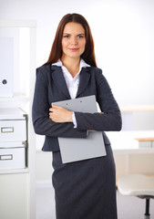 Attractive young businesswoman standing near desk with folder i