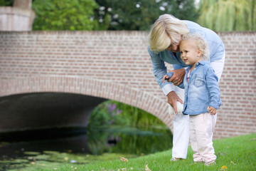 Little girl standing outdoors with grandmother in park