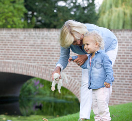 Loving grandmother standing outdoors with little girl