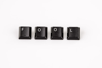 fool word written with black computer buttons over white