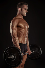 Muscular bodybuilder guy doing exercises with big dumbbell dumbb