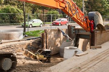 Kanalbauarbeiten - Ein Baggerarm ruht auf einer Verbauplatte
