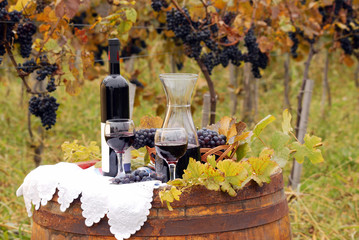 red wine and grape on wooden barrel