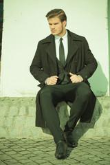elegant business man sitting on a sidewalk