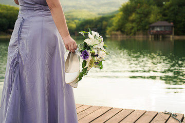 girl on the lake with a bouquet of flowers