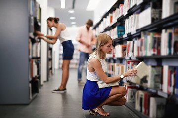 Blonde female college student taking book from shelf in library