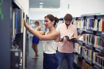 Female college student taking book from shelf in library