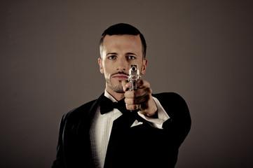 Sexy man in a tuxedo pointing  gun