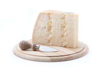 formaggio grana su tagliere rotondo con coltello