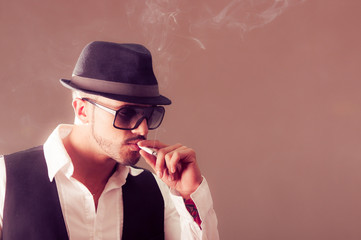 Young handsome stylish male model smoking a cigarette