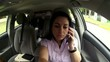 Woman talking on mobile phone in the car driving.