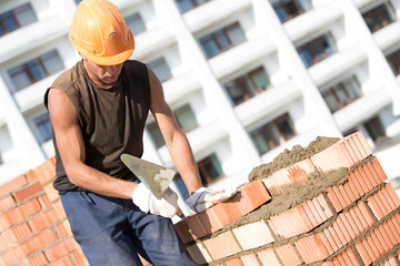 Construction bricklayer worker installing brick with trowel