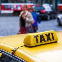 Schild eines Prager Taxis mit unscharfen Menschen im Hintergrund