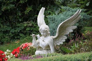Engel musiziert zwischen Blumen auf Friedhof