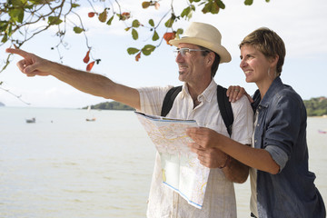 Middle aged couple on vacation with map