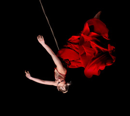 Woman gymnast in red dress on rope on black background