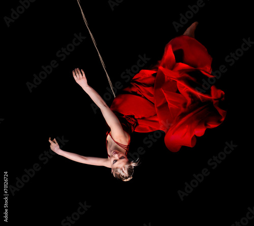 Leinwanddruck Bild Woman gymnast in red dress on rope on black background