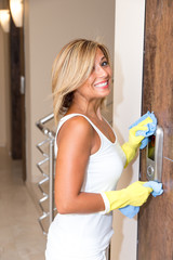 Young woman is cleaning up the house