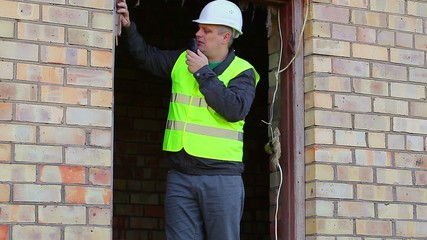 Building inspector talking on a walkie-talkie