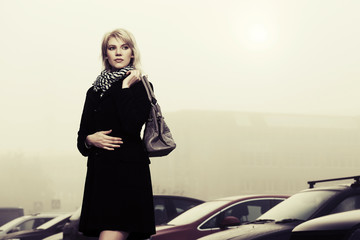 Young fashion woman with handbag on the foggy city street