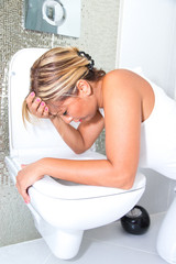 Girl vomiting into the bowl