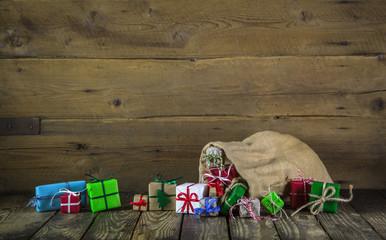 Bunte Weihnachtsgeschenke auf Holz Hintergrund: Gutschein