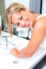 Woman washing her hands in bathroom