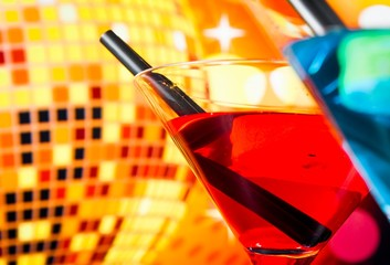 detail of cocktail with sparkling disco ball background