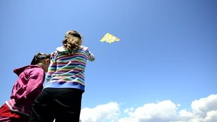 Girls flying kite on blue clear sky