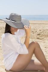 Mujer con vestido blanco y pamela en la playa